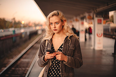 Young thoughtful woman using smart phone while waiting for train - p1166m2153547 by Cavan Images