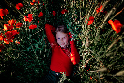 Little girl lying in poppy field - p300m2114825 von Oxana Guryanova