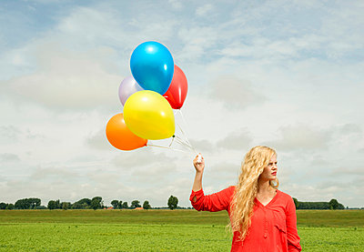 Woman with balloons - p429m929448f by Mischa Keijser