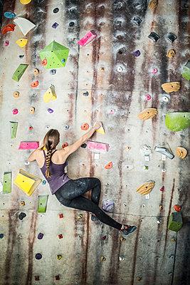 Athlete climbing rock wall in gym - p555m1411956 by John Fedele