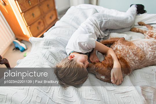 Affectionate boy cuddling dog on bed - p1023m2201139 by Paul Bradbury