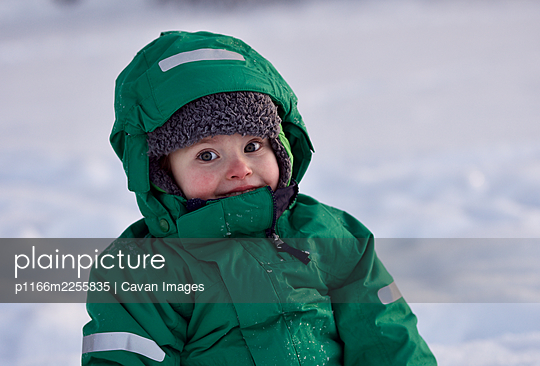 Portrait of smiling little boy playing in snow on cold winter day - p1166m2255835 by Cavan Images