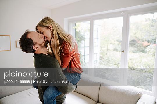 Man lifting and kissing his wife - p300m2166669 von Kniel Synnatzschke