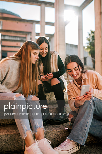 Smiling teenage girl showing mobile phone to friends while sitting on steps - p300m2251616 by LUPE RODRIGUEZ