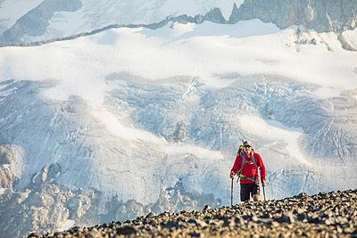 View of hiker against large glacier across valley. - p1166m2153406 by Cavan Images