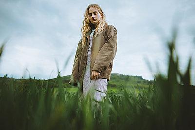 Woman wearing jacket behind grass - p1427m2163652 by Oleksii Karamanov