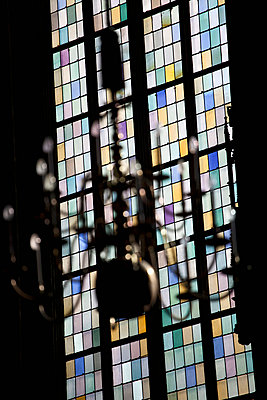 A stained glass window in back of a chandelier, focus on window - p30119832f by Halfdark