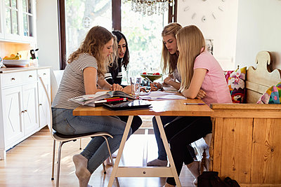 Teenage girls doing homework together at home - p426m1196499 by Maskot