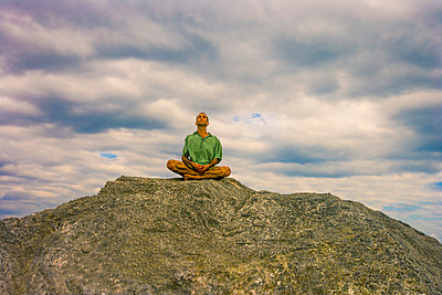 Man meditating on rock under clouds - p555m1301836 by Jed Share/Kaoru Share
