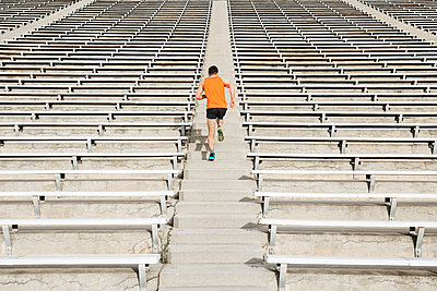 Young male runner running up stadium stairway, rear view - p924m2074676 by JFCreatives