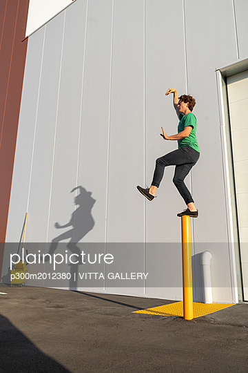 Acrobat standing on pole, casting shadow at cleaning bucket - p300m2012380 von VITTA GALLERY