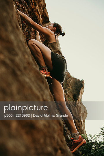 Determinant woman climbing rock mountain in forest - p300m2213962 by David Molina Grande