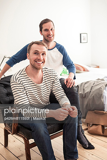 Portrait of happy homosexual couple sitting on chair in bedroom