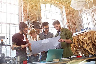 Designers examining blueprints in workshop - p1023m1486405 by Agnieszka Olek