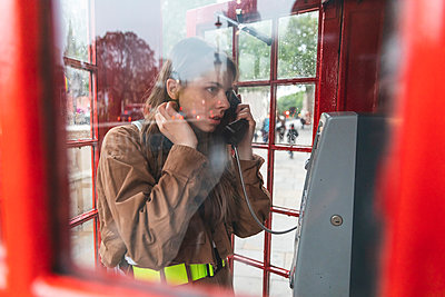 Young woma nmaking a call from a red phone booth in the city, London, UK - p300m2121952 by William Perugini