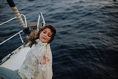 Woman leaning on net while sitting on sailboat during vacation - p300m2274862 by Gala Martínez López