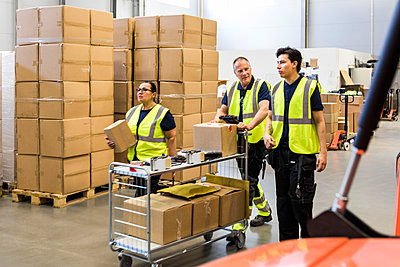 Multi-ethnic coworkers pushing cart at distribution warehouse - p426m2018822 by Maskot