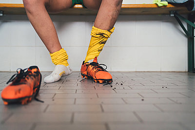 Football player in one football boot in changing room - p429m1578512 by Eugenio Marongiu