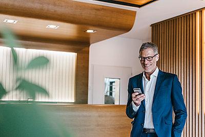 Reifer Geschäftsmann mit Smartphone liest eine SMS - p586m1208511 von Kniel Synnatzschke