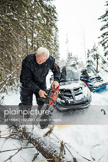 Snowmobiler using chainsaw to clear trails - p1166m2192038 by Cavan Images