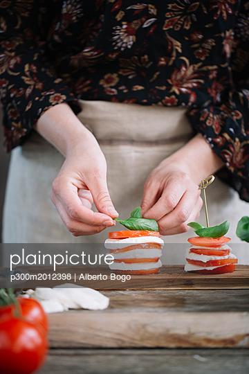 Woman's hands preparing Caprese Salad - p300m2012398 von Alberto Bogo