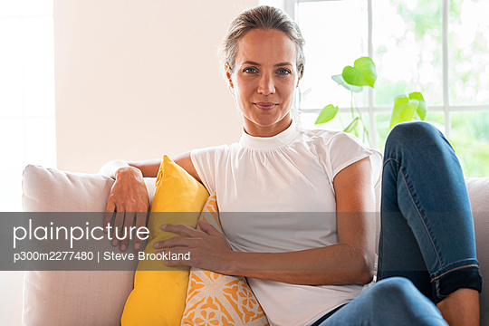 Woman relaxing on couch at home - p300m2277480 by Steve Brookland