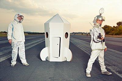 Two boys dressed up as spacemen standing at cardboard rocket - p300m1188559 by Rik Rey