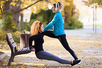 Two sportive young women stretching in park - p300m1563307 by Josep Suria