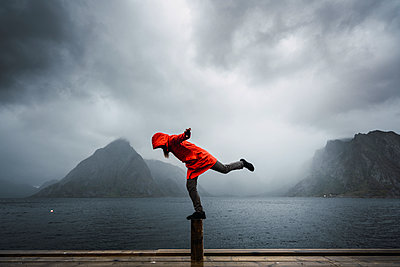 Norway, Lofoten, man balancing on a pole at the coast - p300m2042268 by Kike Arnaiz