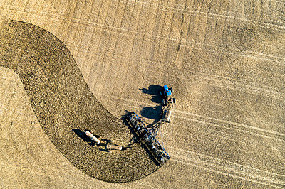 Aerial view of a tractor pulling an air seeder, seeding a field; Beiseker, Alberta, Canada - p442m2037056 by Michael Interisano