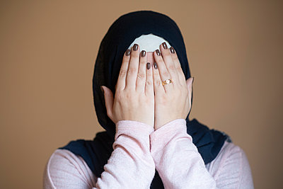 Muslim woman hiding face with hands  - p794m2215932 by Mohamad Itani