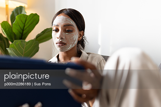 Woman using digital tablet while sitting with beauty mask on face at home - p300m2286189 by Sus Pons