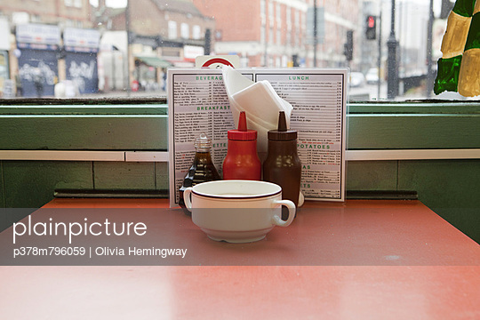 Condiments on cafe table - p378m796059 by Olivia Hemingway