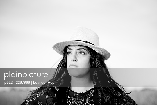 Portrait of black-haired woman with straw hat - p552m2287966 by Leander Hopf