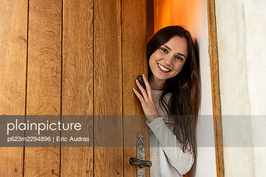 Portrait of smiling young woman standing behind door - p623m2294896 by Eric Audras