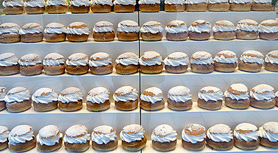 View of almond cream buns displayed in a row for sale - p1025m789016f by Peo Quick