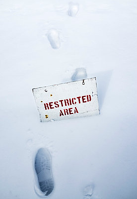 Footprint in the snow with prohibition sign - p1053m793681 by Joern Rynio