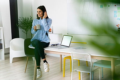 Smiling businesswoman wearing headset drinking coffee while sitting on desk by laptop at office - p300m2251424 by Giorgio Fochesato