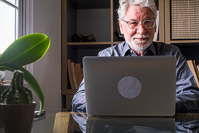 Smiling senior businessman with laptop at home - p300m2276591 by Simona Pilolla