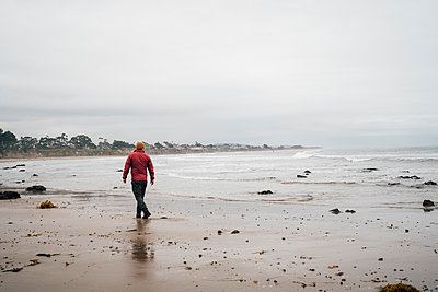 Rear view of man wearing red jacket walking along a sandy beach on a rainy day. - p429m2177005 by Jonas Jungblut