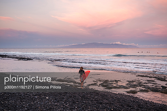 Spain, Tenerife, boy carrying surfboard on the beach at sunset - p300m1192127 by Simona Pillola