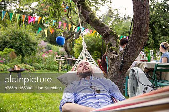 Junger Mann in der Hängematte entspannt sich - p788m1165390 von Lisa Krechting