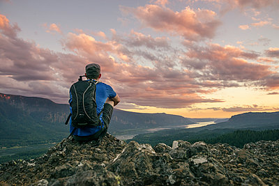 Rear view of hiker with backpack sitting on mountain at Crater Lake National Park - p1166m1415116 by Cavan Images