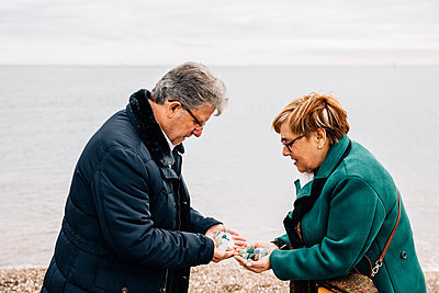 Side view of senior couple showing off stones from the beach - p1166m2078391 by Cavan Images