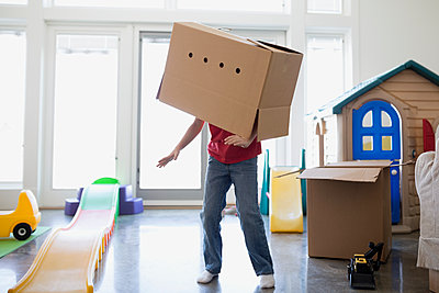 Playful boy dancing with cardboard box on head - p1192m1107750f by Hero Images