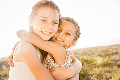 Portrait of two happy cute girls hugging at sunset - p300m2167488 by Floco Images