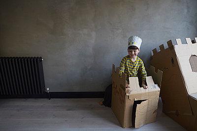 Happy boy playing with cardboard box against wall - p301m1579647 by Liesel Bockl