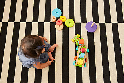 Overhead view of baby girl sitting on rug playing with toy train - p429m1448263 by Emma Kim