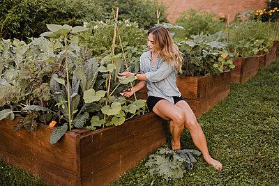 Woman working in her garden - p429m2145965 by Sara Monika