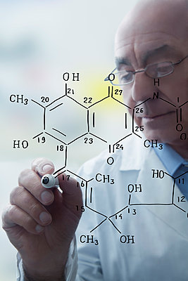 Senior male scientist writing molecular formula on clear board - p924m1022685f by REB Images